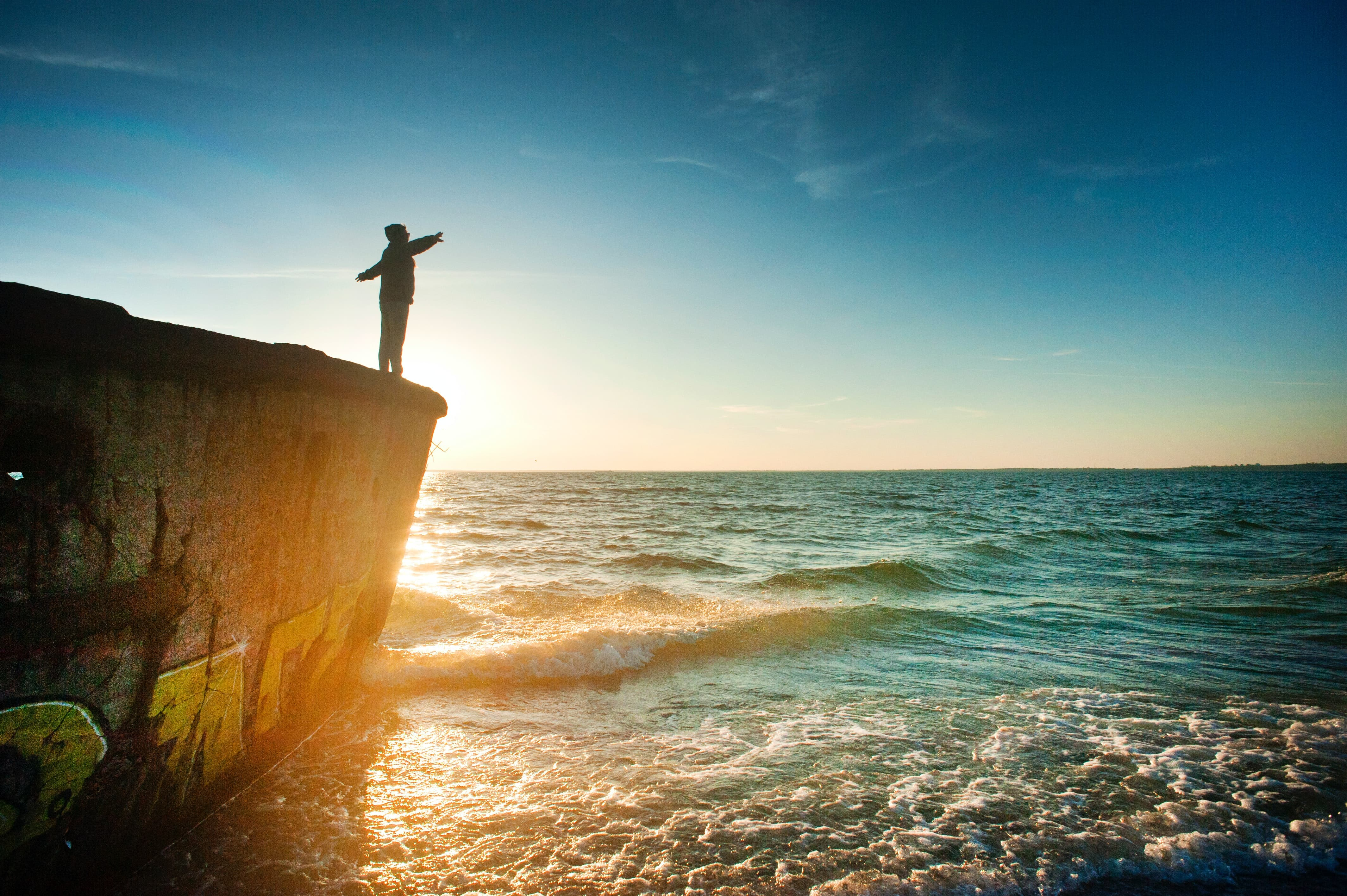 silhouette-of-person-on-cliff-beside-body-of-water-during-1060489 (1)